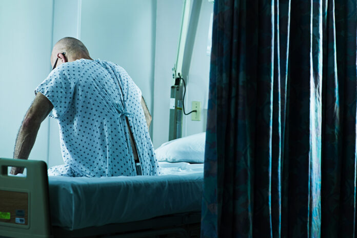 A man in a hospital gown sits on a hospital bed